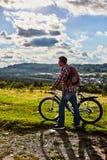 Een mens in aard met een fiets op de achtergrond van bergen en blauwe hemel stock foto