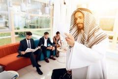 Een mens in Arabische kleren houdt een koffer stock foto