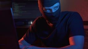 Een mens in balaclava, politie die, cybercrime overvallen stock video