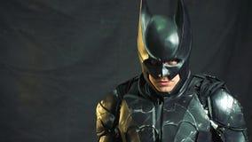 Een mens in een Batman-kostuumtribunes in een ruimte met een donkere doek wordt behandeld, heft zijn hoofd op en bekijkt boos de