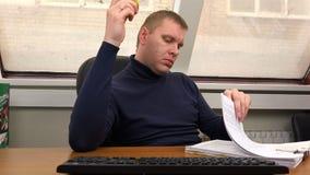 Een mens bekijkt documenten terwijl het zitten bij een lijst in een leunstoel stock videobeelden