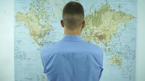 Een mens bekijkt een kaart van de wereld stock video