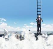 Een mens beklimt op de ladder Wolken en de mening van New York stock afbeeldingen