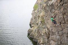 Een mens beklimt op de rots dichtbij het water royalty-vrije stock foto