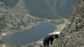 Een mens beklimt een rots op een achtergrond van bergmeren stock footage