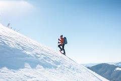 Een mens beklimt tot de bovenkant van de berg royalty-vrije stock foto's