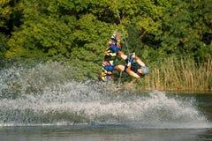 Een mens belast met wakeboard op het meer voert sprongen uit stock fotografie