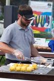 Een mens bereidt een suikermaïs op een grill voor Stock Afbeelding