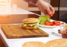 Een mens bereidt een snel voedselhamburger in een moderne keuken, cheeseburger, close-up voor stock fotografie