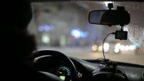 Een mens berijdt een de winterauto door auto in de stad, stadslichten, sneeuw stock footage