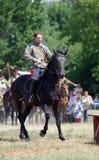 Een mens berijdt een zwart paard De concurrentie van paardruiters Royalty-vrije Stock Foto's