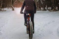 Een mens berijdt een fiets in de winter in de sneeuw royalty-vrije stock afbeelding