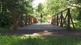 Een mens berijdt een fiets over de brug in het park Langzame Motie stock videobeelden