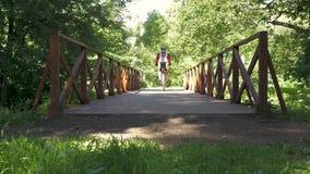 Een mens berijdt een fiets over de brug in het park Langzame Motie stock video