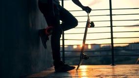 Een mens berijdt een skateboard op een zonsondergangachtergrond, langzame motie stock video