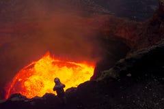 Een mens in een beschermend kostuum dichtbij de mond van de vulkaan Onderzoek van de vulkaan royalty-vrije stock afbeeldingen