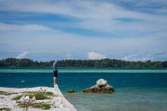 Een mens bevindt zich alleen op de rand van het strand op Harapan-Eiland, Indonesië Een mens is droevig en enkel zich bevindt nog stock foto