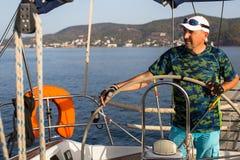 Een mens bevindt zich bij het roer en stelt het varende schip in werking Sport royalty-vrije stock afbeelding