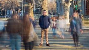 Een mens bevindt zich bij een voetgangersoversteekplaats rond onscherpe mensen en onscherpe auto's De video van de tijdtijdspanne stock footage