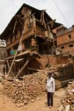 Een mens bevindt zich buiten zijn nu aardbeving geruïneerd huis in Bhaktapu Stock Foto