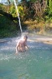 Een mens bevindt zich in de pool met mineraalwater onder de kraan Stock Afbeelding
