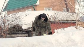 Een mens bevindt zich in de sneeuw in het dorp stock videobeelden