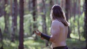 Een mens bevindt zich in het hout en houdt een groot mes en bekijkt hem Dan rond kijkt hij stock videobeelden