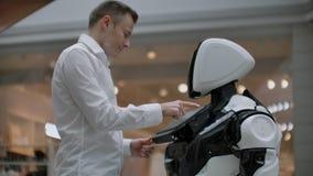 Een mens bevindt zich met een robot bot en stelt hem vragen en vraagt om hulp door op het scherm op het robotlichaam te klikken stock video