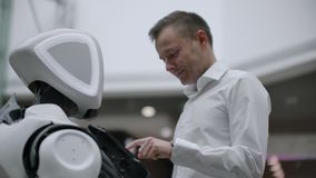 Een mens bevindt zich met een robot bot en stelt hem vragen en vraagt om hulp door op het scherm op het robotlichaam te klikken stock footage