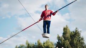 Een mens bevindt zich met zijn voeten in het bekken en springt op de kabel boven de grond Koele en gevaarlijke stunts stock video