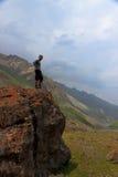 Een mens bevindt zich op een rots. Stock Afbeelding