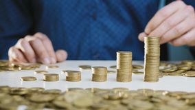 Een mens beweegt een kolom van muntstukken stock footage