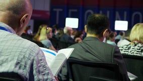 Een mens bij een bedrijfsseminarie luistert aan de spreker en leest het tijdschrift De conferentievergadering van het bedrijfsmen stock footage