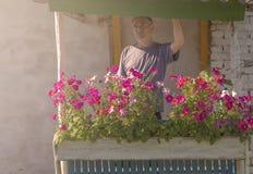 Een mens bij dageraad bevindt zich op de portiek van het huis Stock Fotografie