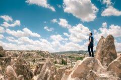 Een mens bij de bovenkant van een heuvel in Cappadocia in Turkije kijkt omhoog aan de verbazende wolken Reis, succes, vrijheid, v Stock Foto's