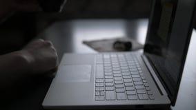Een mens bij de lijst werkt in de avond aan laptop door het venster en drinkt koffieclose-up stock footage