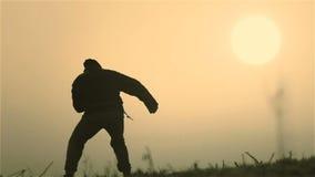 Een mens bij zonsopgang leidt het doen van oefeningen op Gebaarde mens bij dageraad stock videobeelden