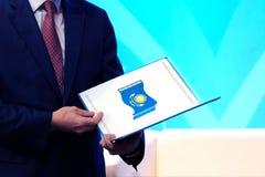 Een mens in een blauw kostuum houdt een open omslag met het beeld van de nationale vlag van de Republiek Kazachstan Het concept a stock foto