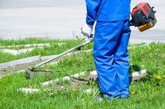 Een mens in blauwe werkende overall maait het gras met een grasmaaimachine stock fotografie