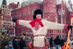 een mens in een bonthoed en in Russische nationale kostuumtribunes naast Moskou het Kremlin stock fotografie