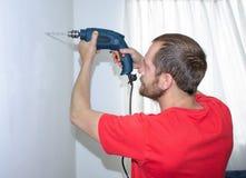 Een mens boort een muur met een boor stock foto's