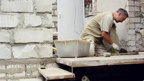 Een mens bouwt thuis een muur stock videobeelden