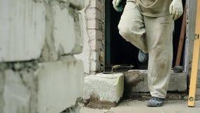 Een mens bouwt thuis een muur stock video