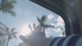 Een mens breidt zijn hand tot de zon uit door het venster van een auto stock video