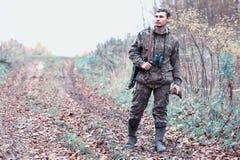 Een mens in camouflage en met een de jachtgeweer in een bos op SP Royalty-vrije Stock Foto