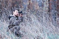 Een mens in camouflage en met een de jachtgeweer in een bos op SP Royalty-vrije Stock Fotografie