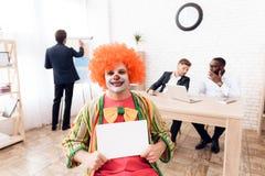 Een mens in een clownkostuum en een pruik zit in het bedrijfsbureau op 1 April Stock Foto's