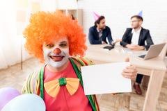 Een mens in een clownkostuum en een pruik zit in het bedrijfsbureau op 1 April Stock Foto