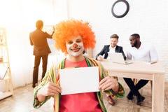 Een mens in een clownkostuum en een pruik zit in het bedrijfsbureau op 1 April Stock Afbeeldingen