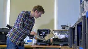 Een mens controleert 3d-druk met zijn laptop stock video